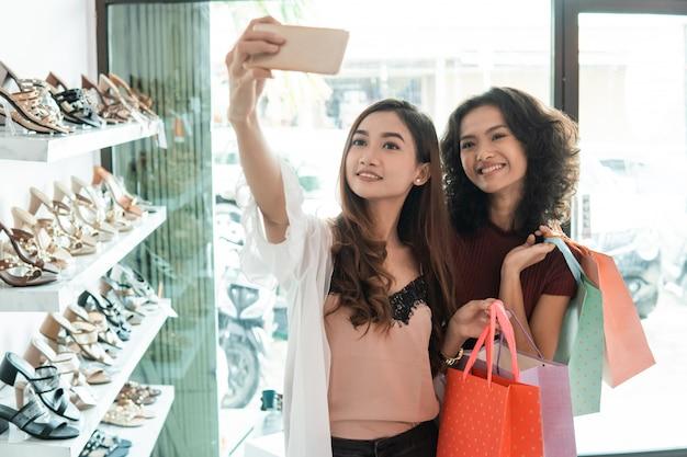 Due amici di donne che prendono un selfie durante lo shopping