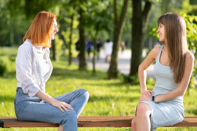 Due amici di ragazze che si siedono su un banco nel parco di estate che chiacchierano felicemente
