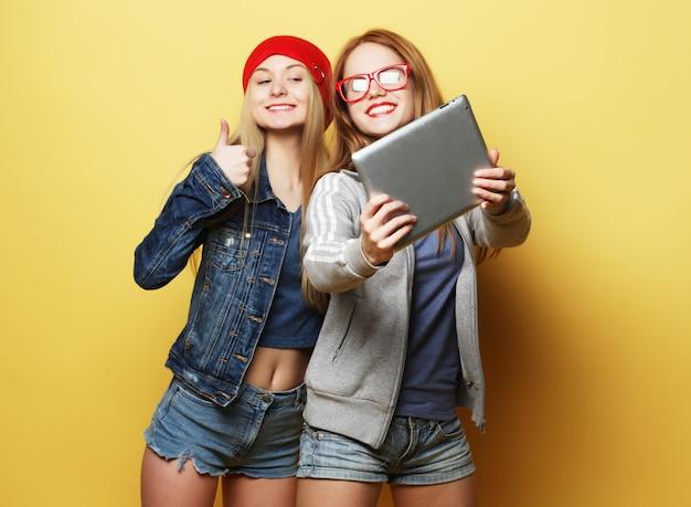 Due amici di ragazze dei pantaloni a vita bassa che prendono selfie con la compressa digitale