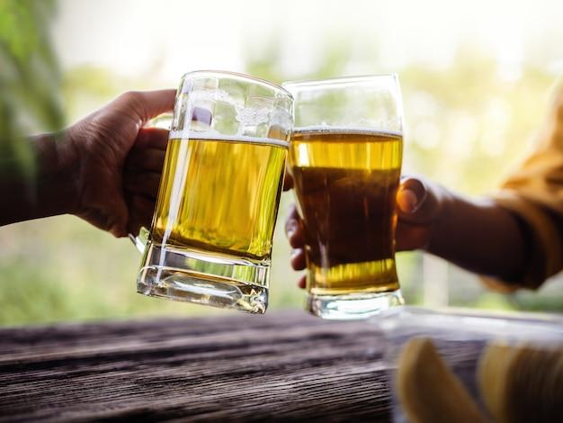 Due amici facendo acclamazioni con gli occhiali e bevendo birra al balcone in estate