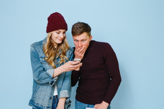 Due amici felici che sono eccitati con i telefoni nelle loro mani isolati su uno sfondo blu