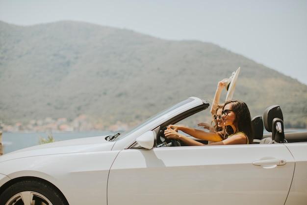 Due amici felici in auto cabriolet bianca guida e in cerca di libertà e divertimento