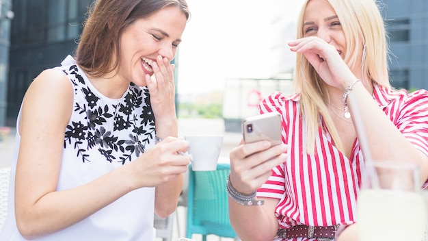 Due amici femminili che godono al caffè all'aperto