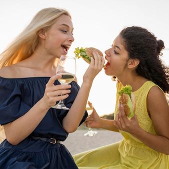 Due amici femminili che mangiano hamburger in spiaggia con vino