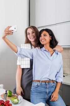 Due amici femminili che prendono selfie sul telefono cellulare in cucina