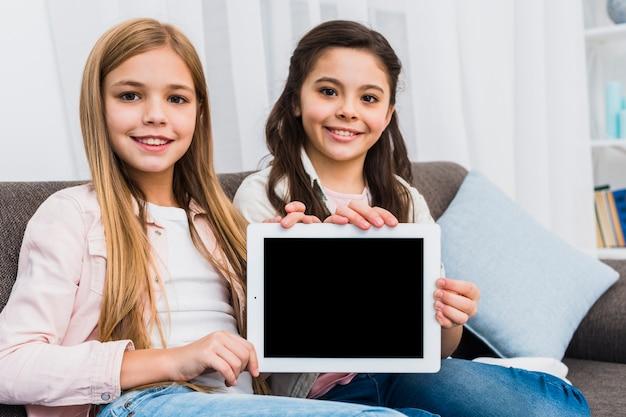 Due amici femminili che si siedono sul sofà che mostra compressa digitale dello schermo in bianco verso la macchina fotografica