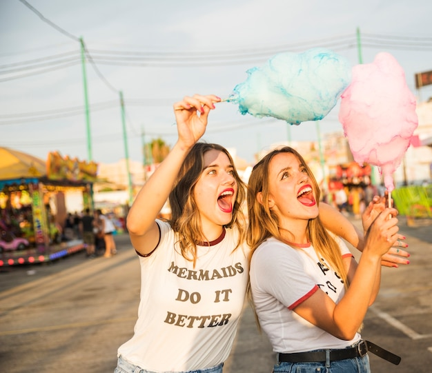 Due amici femminili con zucchero filato divertendosi al parco di divertimenti