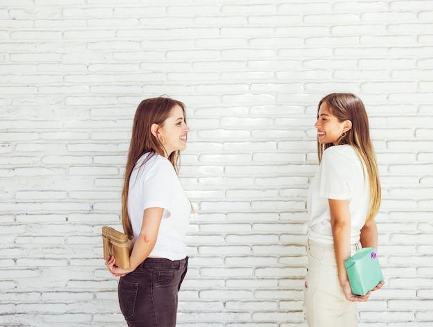 Due amici femminili felici che nascondono il regalo di compleanno l'un l'altro