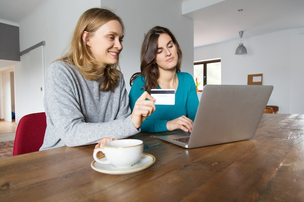 Due amici femminili felici che per mezzo del computer portatile