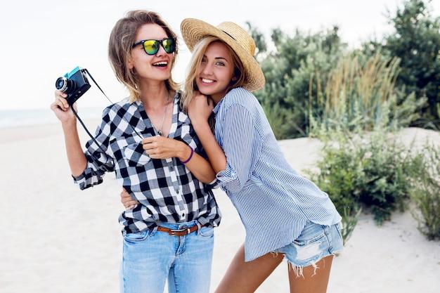 Due amici femminili felici divertendosi sulla spiaggia