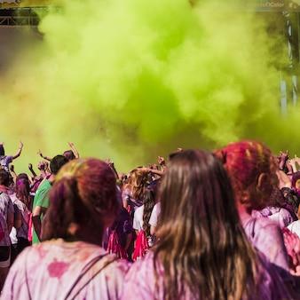 Due amici femminili guardando le persone che ballano nell'esplosione di colori holi
