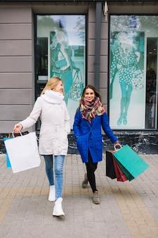 Due amici femminili in cappotto invernale alla moda che tiene i sacchetti della spesa variopinti