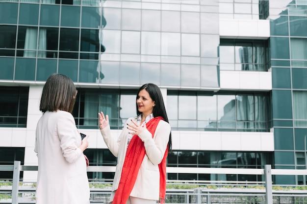Due amici femminili parlando di fronte all'edificio