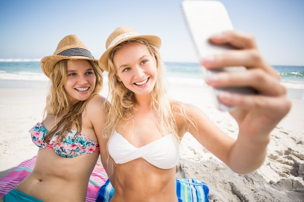 Due amici in bikini che prendono un selfie