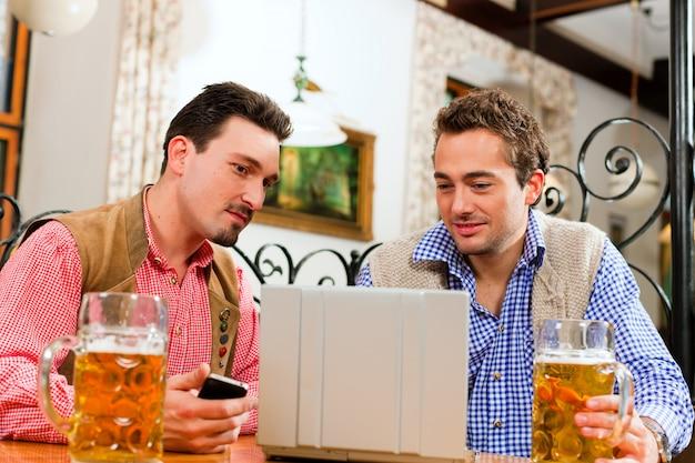 Due amici in un pub bavarese con computer portatile