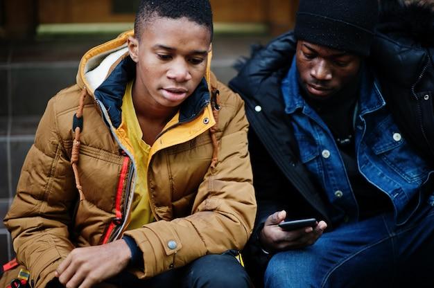 Due amici maschii africani che si siedono insieme e che guardano sul telefono.
