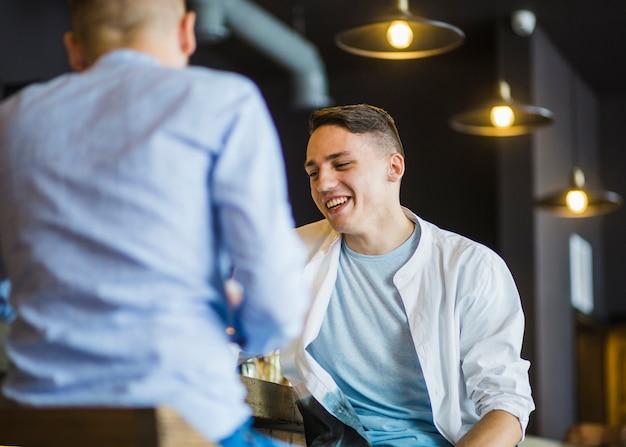 Due amici maschii che si siedono nel ristorante