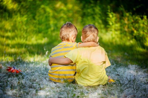 Due amici ragazzini si abbracciano nel giardino estivo. brothe