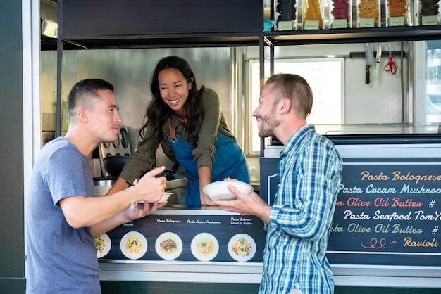 Due amici si divertono a mangiare la pasta dal camion di cibo