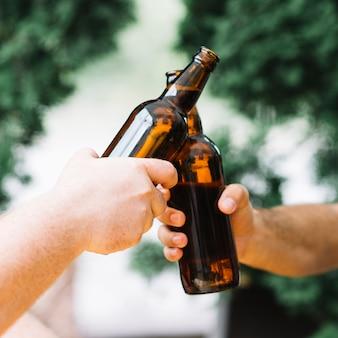 Due amici tintinnano le bottiglie di birra all'aperto