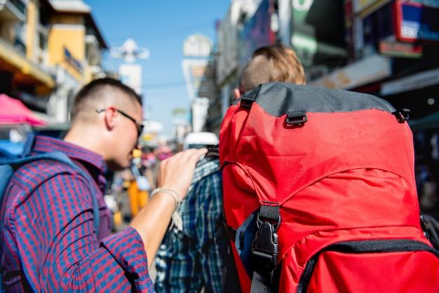 Due amici turistici di viaggiatore con zaino e sacco a pelo che viaggiano in strada di khao san, bangkok tailandia