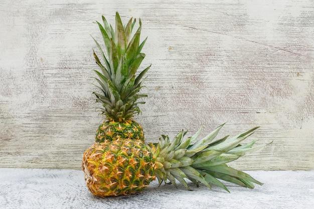 Due ananas aromatici sulla parete grigia e sgangherata, vista laterale.