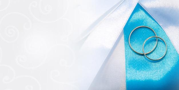 Due anelli di matrimoni sullo sfondo del tessuto