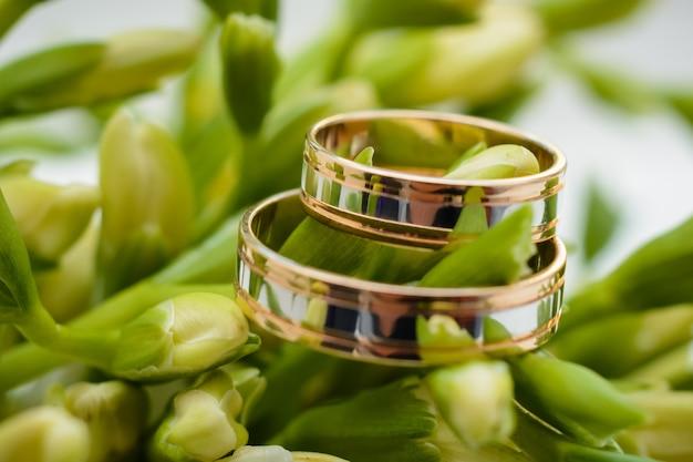 Due anelli di nozze d'oro si trovano sui fiori di un bellissimo bouquet