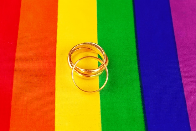Due anelli di nozze d'oro sulla bandiera arcobaleno lgbt.