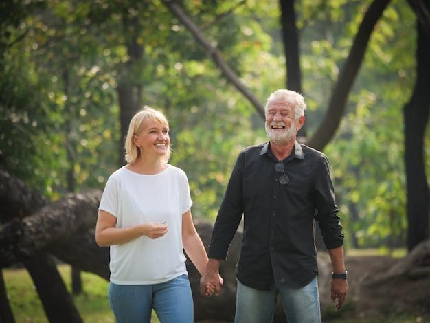Due anziani pensionati felici l'uomo e la donna stanno camminando e parlando nel parco