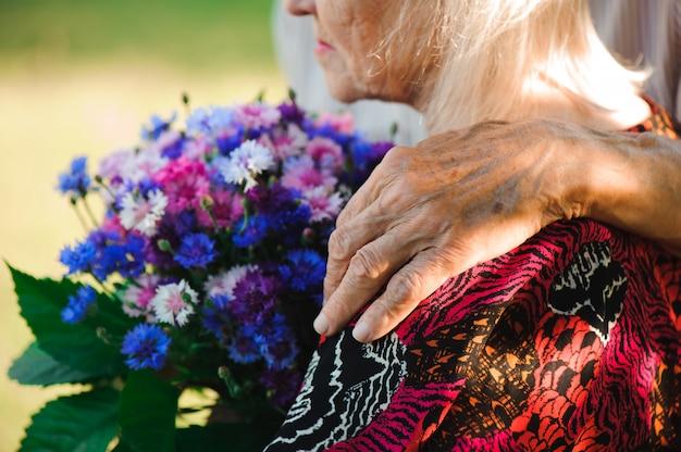 Due anziani si rilassano e si abbracciano in un parco