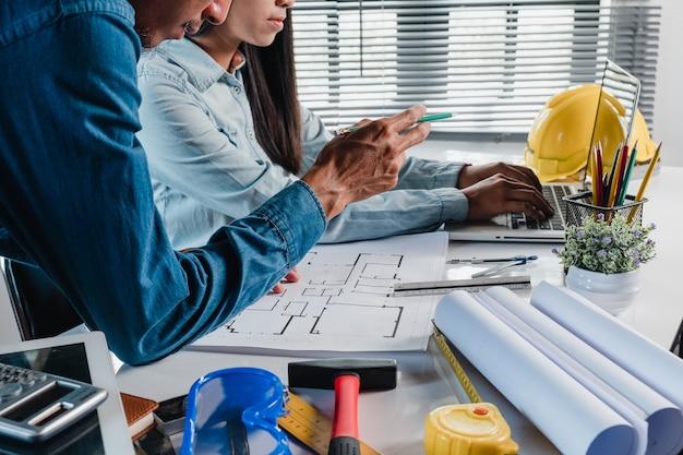 Due architetti che lavorano e discutono di dati con laptop e progetto sul progetto architettonico
