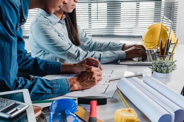 Due architetti che lavorano e discutono di dati e laptop sul progetto architettonico in ufficio