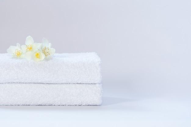 Due asciugamani piegati bianchi con fiori di gelsomino