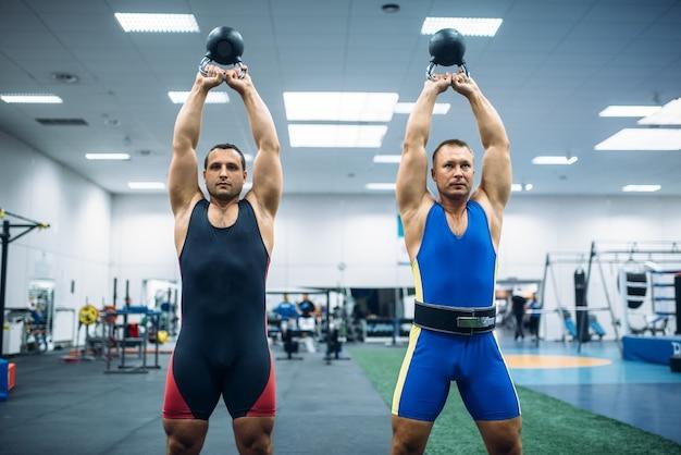 Due atleti maschi hanno sollevato kettlebell sopra le loro teste