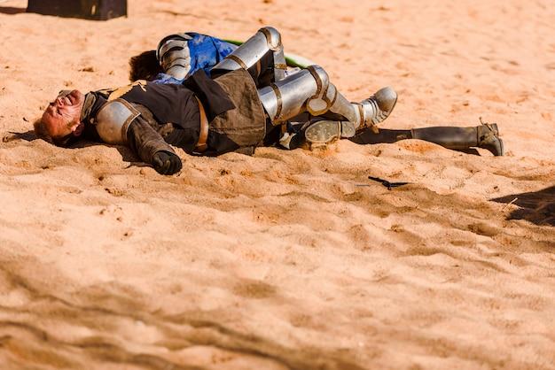 Due attori travestiti da cavalieri medievali distesi a terra sconfitti dopo una battaglia con la spada in un'esibizione