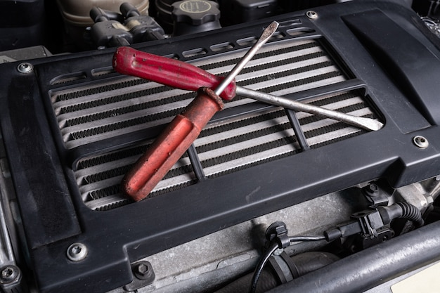 Due avvitatori di metallo giacciono sotto il cofano di un'auto su un radiatore dell'olio. concetto di riparazione auto e strumenti nel servizio auto