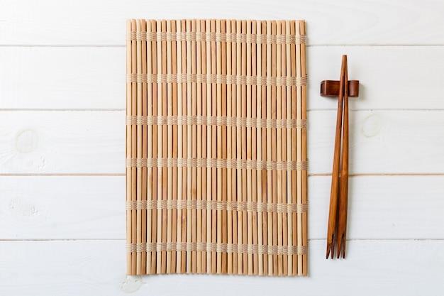 Due bacchette sushi con stuoia di bambù vuota o piatto di legno su legno