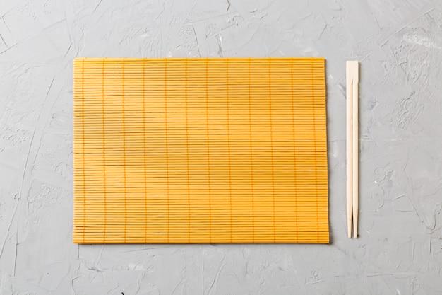 Due bacchette sushi con stuoia di bambù vuoto o piatto di legno su sfondo di pietra vista dall'alto con copia stace