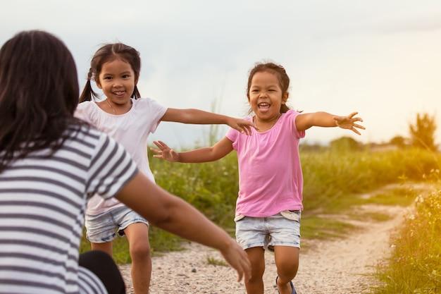 Due bambine asiatiche in esecuzione a loro madre per dare un abbraccio nel parco