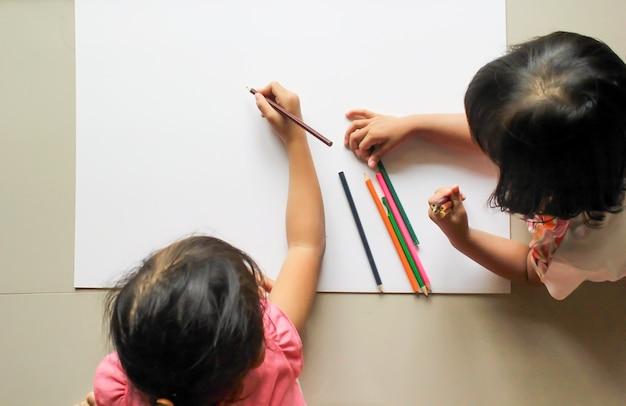 Due bambine che disegnano con la matita di colore sul libro bianco