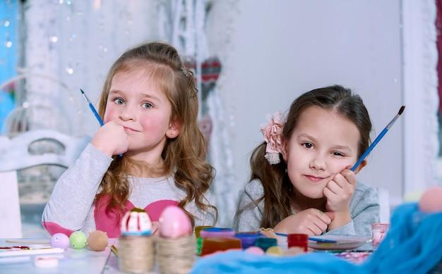 Due bambine con i pennelli in mano pensando e non sanno cosa disegnano. concetto di crisi creativa.