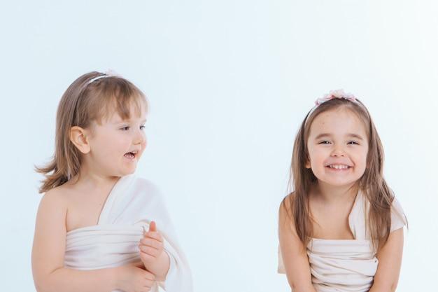 Due bambine con la bocca spalancata su uno sfondo bianco. i bambini stanno giocando. il concetto di educazione, infanzia, emozioni, odontoiatria, sorpresa, amicizia. copia spazio