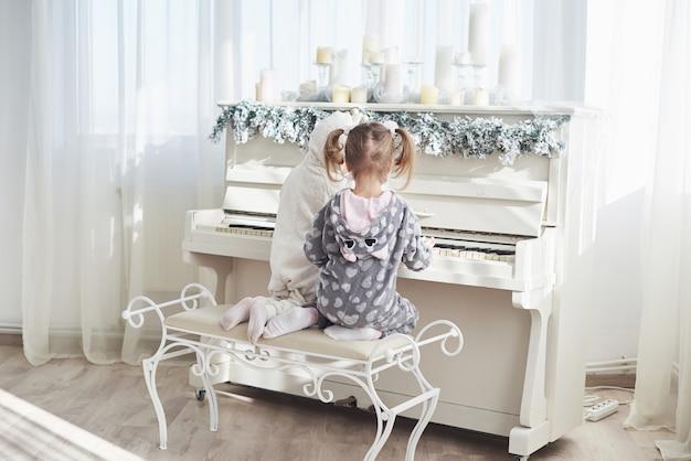 Due bambine felici in pigiama suonano il piano il giorno di natale