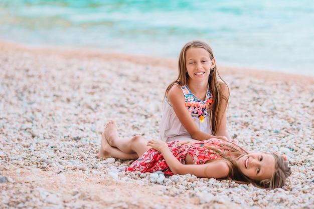 Due bambine felici si divertono molto in spiaggia tropicale giocando insieme