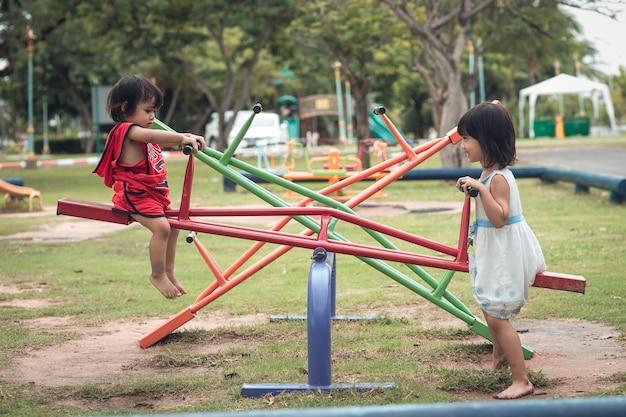 Due bambine felici su bordo oscillante all'aperto