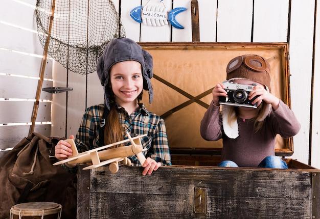 Due bambine-piloti in una grande cassa di legno