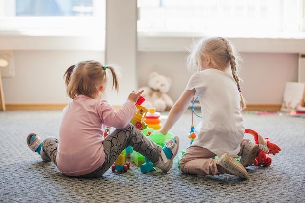 Due bambine sedute sul pavimento a giocare