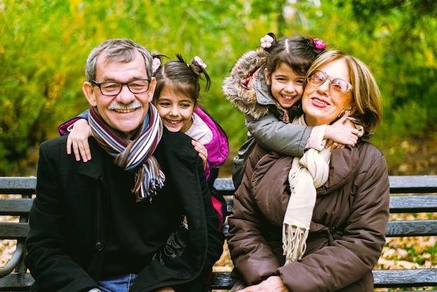 Due bambine si siedono nel parco d'autunno con i suoi nonni su una panchina
