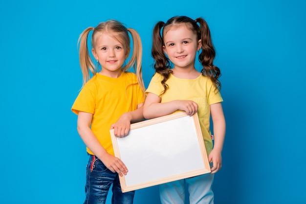 Due bambine sorridenti con un tavolo da disegno vuoto su sfondo blu